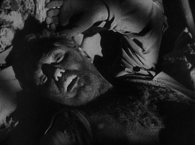 Düstere Nahaufnahme des eingeklemmten Leo Minosa in der Höhle.