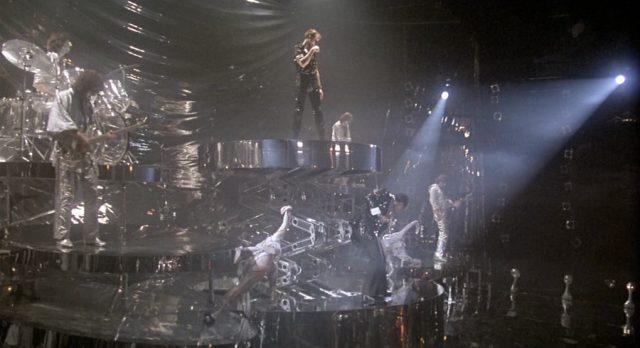 Gideon auf einem hinauffahrenden Podest in einer schrillen Szenerie aus Chrom- und Silbertönen im Beisein einer spielenden Band.