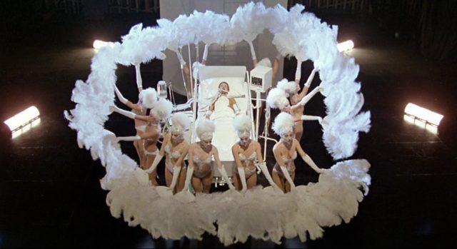 Eine Gruppe knapp bekleideter Tänzerinnen umringt das Krankenbett mit Joe Gideon darin und schwingt weiße Federwedel.