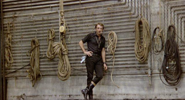 Gideon lehnt in erschöpfter Körperhaltung an einer vergitterten Wand, an der Seile hängen.
