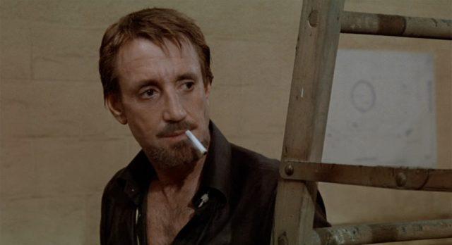 Nahaufnahme von Roy Scheider als Joe Gideon, der mit einer im Mundwinkel herabhängenden Zigarette mit verlorenem Blick in einen nicht sichtbaren Raum starrt.