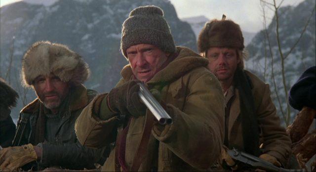 Drei Schergen von Hazel in Winterkleidung, wobei der mittlere eine doppelläufige Shotgun im Anschlag hat.