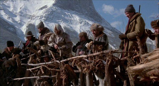 Menschengruppe in dicker Winterbekleidung vor dem Hintergrund einer verschneiten Berglandschaft.