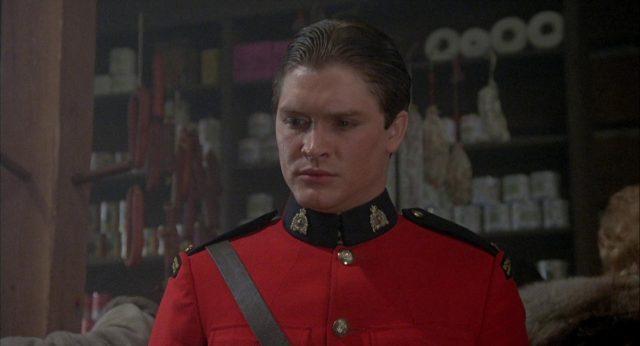 Nahaufnahme von Constable Stevens in der roten Uniform der kanadischen Bergpolizei mit bedächtigem Blick nach schräg unten.