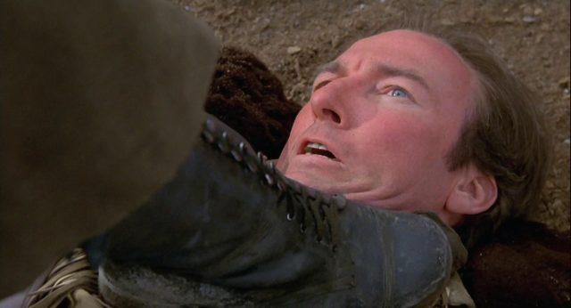 Nahaufnahme von Hazel, der von Johnsons Stiefel zu Boden gedrückt wird.