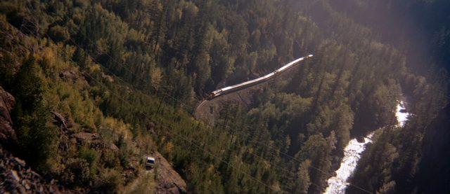Blick aus Vogelperspektive auf den Passagierzug, der sich durch die bewaldete Wildnis der Rocky Mountains schlängelt.