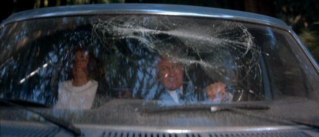 Nahaufnahme von Hunnicutt und Caulfield in einem Geländewagen mit beschädigter Windschutzscheibe.