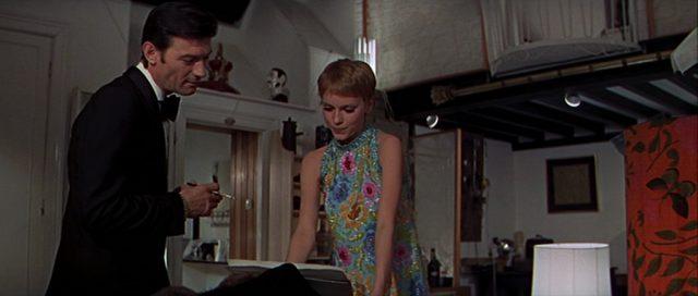 Eberlin mit Zigarette in der Hand im Beisein von Caroline in farbenfrohem Kleid.