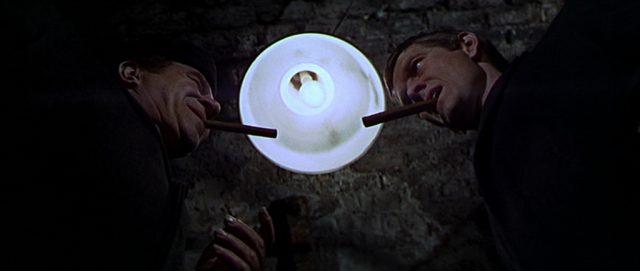 Sobakevich und Gatiss mit Ziagrren im Mund unter einer leuchtenden Lampe, betrachtet aus der Froschperspektive.