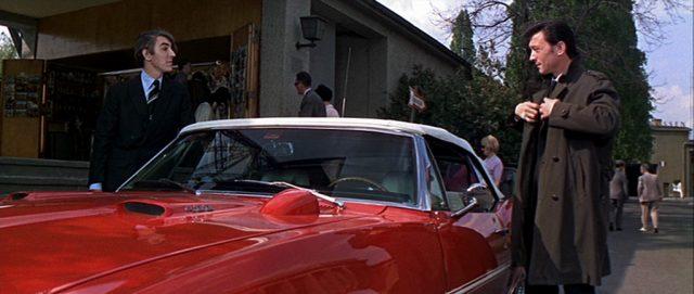 Peter Cook als Prentiss und Eberlin an einem roten Roadster mit weißem Verdeck.