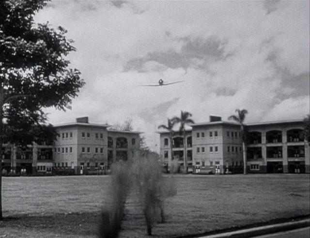 Japanischer Jagdbomber im Flub über das Kasernengelände, im Vordergrund durch die Maschinengewehrgarben hochspritzende Erde.