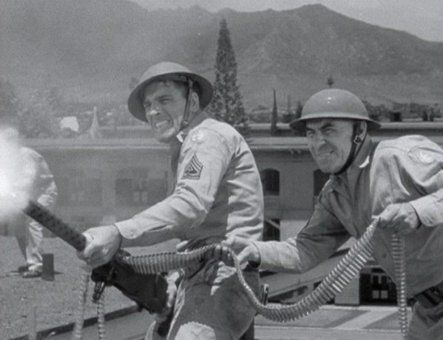 Burt Lancaster in der Pose eines Action-Helden als Sergeant Warden, der während des japanischen Angriffs auf Pearl Harbor mit der Hilfe eines Kameraden mit seinem Maschinengewhr feuert.