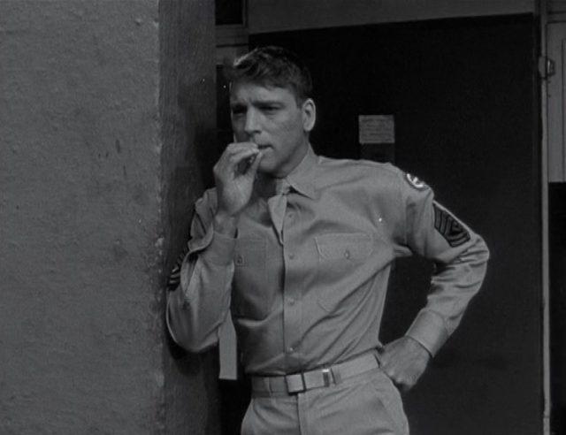 Burt Lancaster als Sergeant Milton Warden lehnt lässig mit Zigarette an einemm Wandvorsprung.