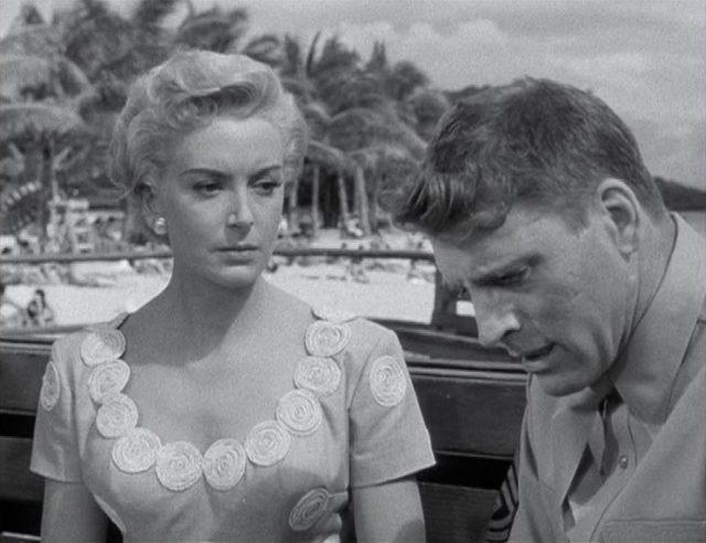 Deborah Kerr und Burt Lancaster als heimliches Liebespaar mit ernsten Mienen im Gespräch vor idyllischem Hintergrund mit Sandstrand und Palmen in Hawaii.