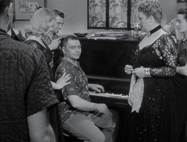 Ernest Borgnine als Sergeant Judson, der in einer Partygesellschaft in Zivilkleidung am Klavier sitzt.