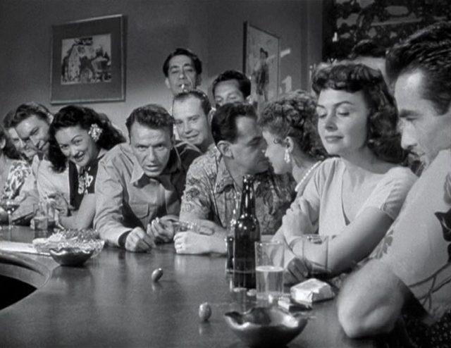 Frank Sinatras als Maggio mit zornigem Gesichtsausdruck an einer Bar inmitten Feiernder.