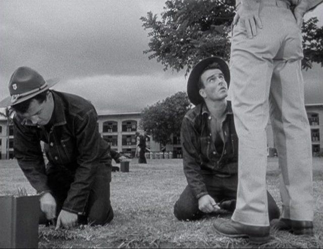 Montgomery Clift als Robert E. Lee Prewitt auf dem Kasernenrasen bei der Strafarbeit; vor ihm bauen sich die beiden Beine eines Vorgesetzten auf.