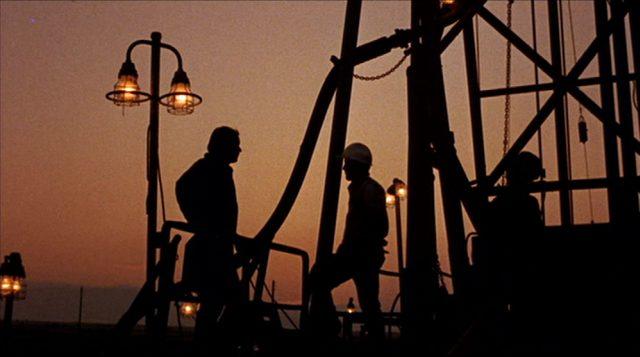Silhouetten von Ölarbeitern an einem Bohrturm in der Dämmerung.