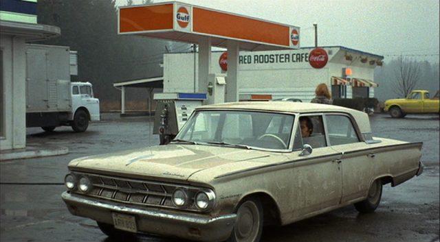Limousine mit verschmutzter Karrosserie an einer Tankstelle in verregneter Szenerie.