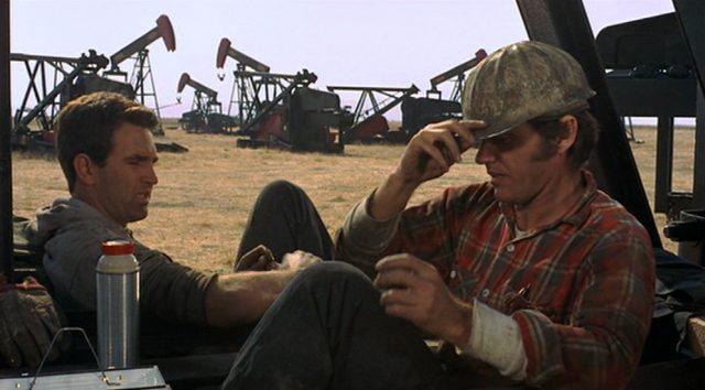 Dupeas Kumpel und Arbeitskollege Eltin bei der Pause mit Dupea, im Hintergrund einige Ölpumpen.