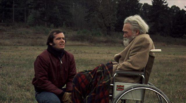 Robert Dupea kniet auf einer Wiese in pessimistischem Licht vor seinem teilnahmslos dreinblickenden Vater im Rollstuhl.