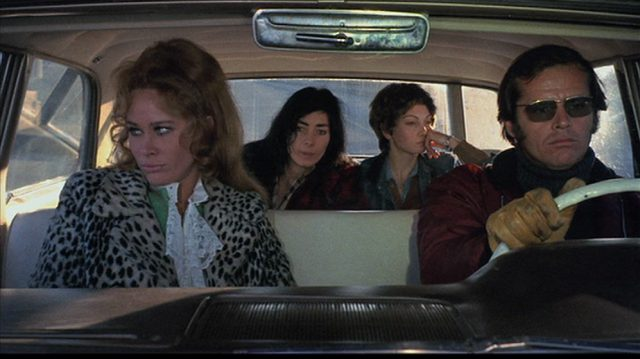 Karen Black als Rayette und Jack Nicholson als Robert im Auto, auf der Rückbank zwei Anhalterinnen.