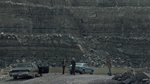 In einem Steinbruch stehen sich neben zwei geparkten Fahrzeugen Conway, der Broker und dessen Scherge Karl gegenüber.