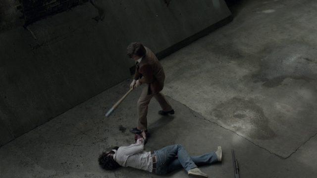 Buddy mit einem Baseballschläger in einer verlassenen Industriehalle, vor ihm ein zu Tode geprüfeltes Opfer voller Blut.