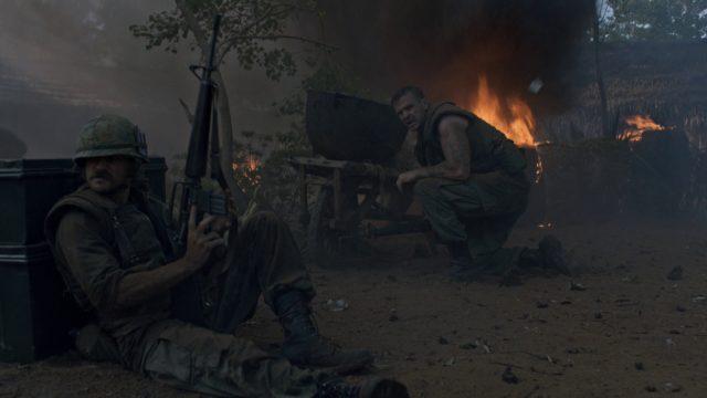 Zwei Marines im Gefecht in einem vietnamesischen Dorf, im Hintergrund lodern Flammen.