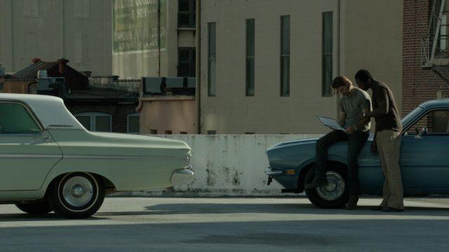Mac und sein Kumpel Arthur lehnen an einem Fahrzeug und betrachten eine Mappe mit den Instruktionen für ihren ersten Mordauftrag.
