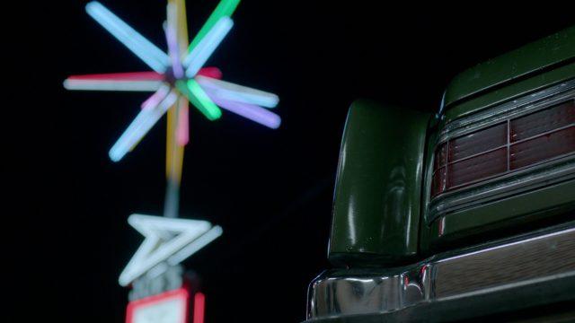 Im Hintergrund ein buntes Neonlichtensemble, im Vordergrund die Ecke der Vorderseite eines Fahrzeugs.