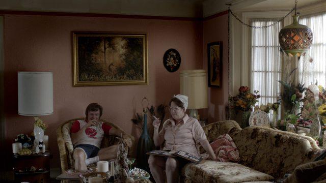 Buddy und seine Mutter Naomi sitzen in ihrem mit lauter Kitsch vollgestellten Wohnzimmer; an der Wand prangt in goldenem Rahmen ein Ölgemälde mit Wildmotiv; vor Naomi, die ein Fotoalbum auf dem Schoß hat, steht eine überfüllte Schale mit Zigarettenstummeln.