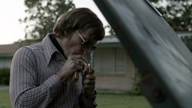Buddy steht mit Sonnebrille am geöffneten Kofferraum und zündet sich eine Zigarette an.