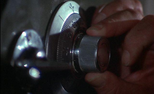 Close-up einer Hand, die am Zahlenschloss eines Safes dreht.
