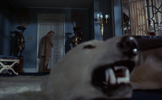 Blick auf Henry Clarke, der an einer Tür lauscht, im Vordergrund der konservierte Kopf eines zum Teppich verarbeiteten Eisbären.