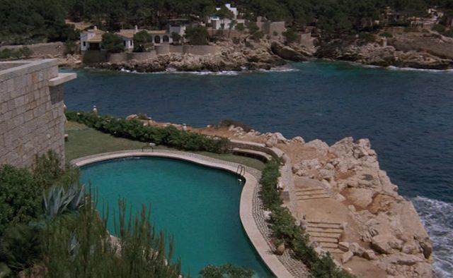 Blick auf den Swimmingpool eines mediterranen Anwesens in einer Bucht von Mallorca.