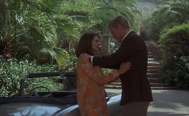 Giovanna Ralli und Michael Caine als heimliches Liebespaar Fé und Henry am Jaguar E-Type vor idyllischem Hintergrund.