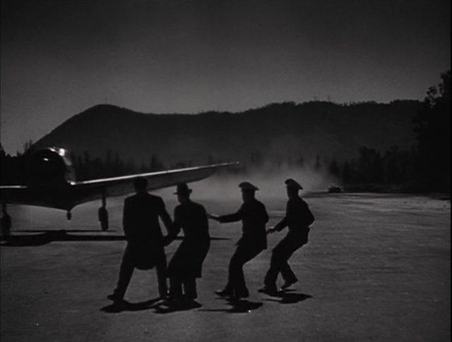 Eine Einpropellermaschine startet im Dunkel der Nacht, während vier Polizisten dem herannahenden Flugzeug ausweichen.