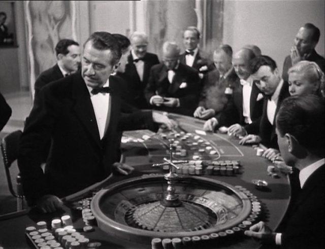 Ein Croupier am Roulettetisch mit Gästen vermittelt die Casino-Atmosphäre.