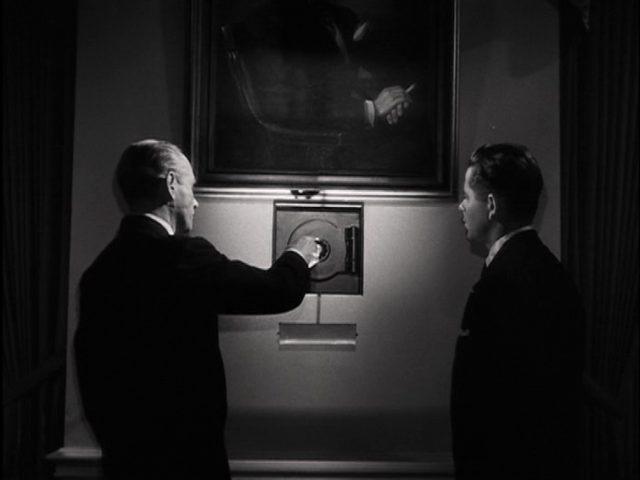 Farrell schaut zu, wie im mysteriösen Dunkel von Munsons Büro ein Safe geöffnet wird.