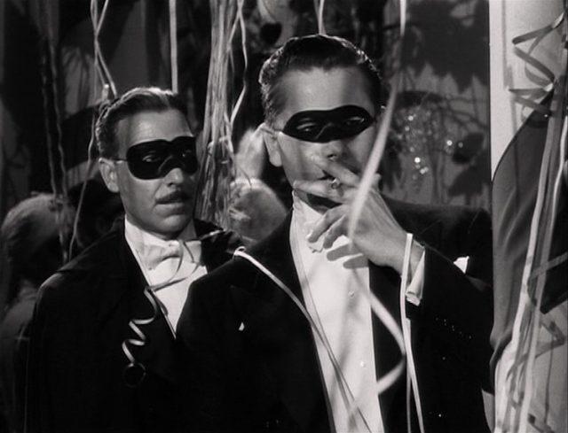 Farrell in Begleitung eines Kriminalkommissars; beide sind anlässlich einer Party maskiert.