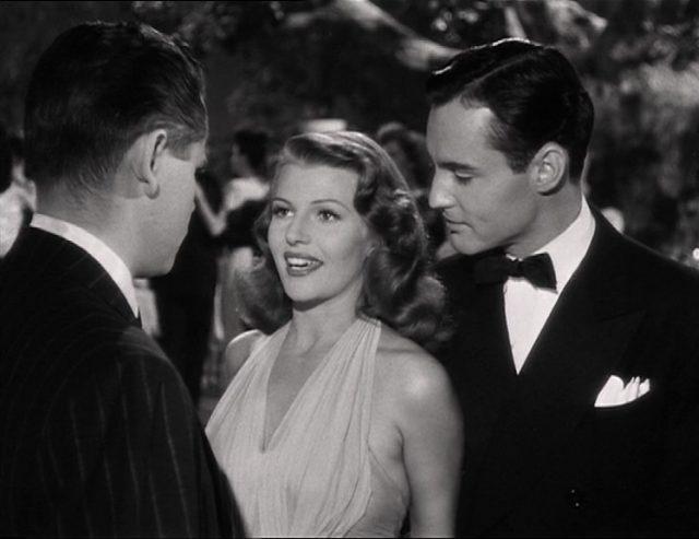 Gilda mit Lächeln in der Konfrontation mit Johnny; begleitet wird sie von einem ihrer Liebhaber.