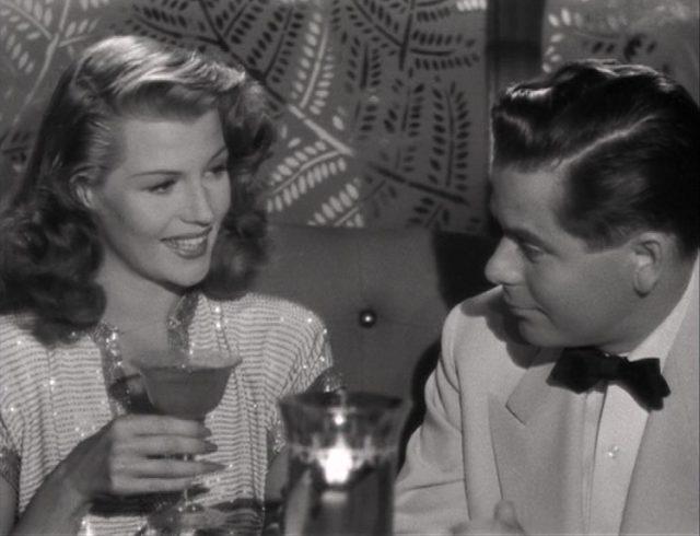 Rita Hayworth hält als Gilda ein gefülltes Cocktailglas in der rechten Hand und lächelt in Richtung des neben ihr sitzenden Johnny Farrell.