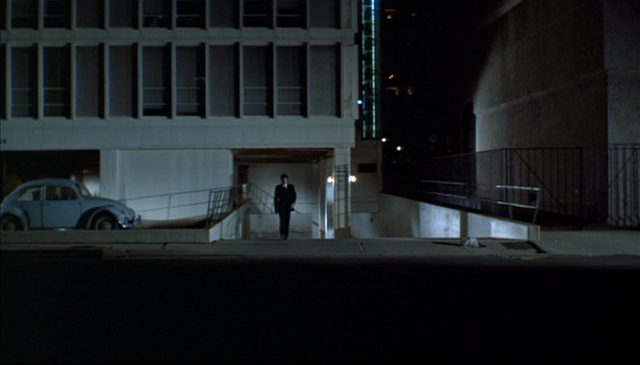 Nachtaufnahme eines Gebäudes, vor dem ein VW Käfer parkt und aus dem Scorpio gerade herausgeht.