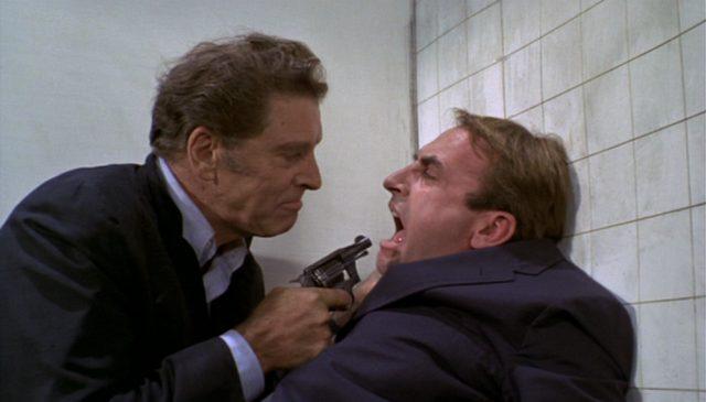Burt Lancaster als CIA-Agent Cross, der mit einem Revolver einen Mann, gespielt von James Sikking, bedroht.