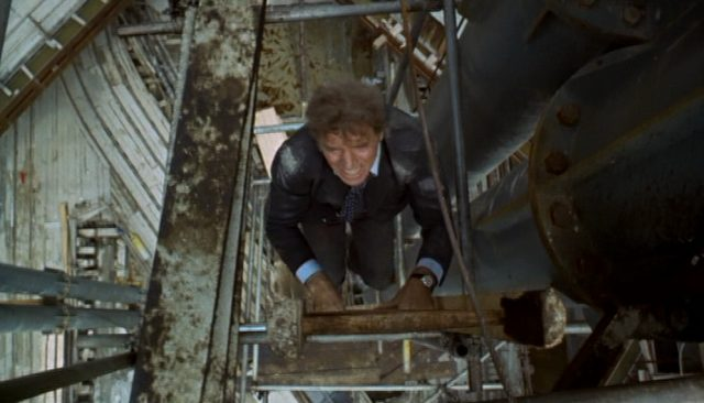 Cross klettert mit verschmutztem Sakko und angestrenter Miene an einer Leiter auf einer Baustelle in Wien.