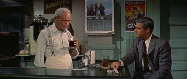 Ein älterer Mann bedient an den Tresen eines Diners, ihm gegenüber sitzt ein im Anzug gekleideter Kunde.