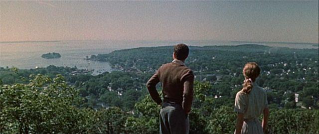 Zwei Menschen blicken von einem Hügel auf die Stadt herab.