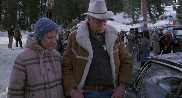 Sheriff Buster und Virginia, gespielt von Frances Sternhagen, blicken skeptisch auf das im Schnee geborgene Fahrzeugwrack, im Hintergrund steht eine Menchentraube im verschneiten Colorado.