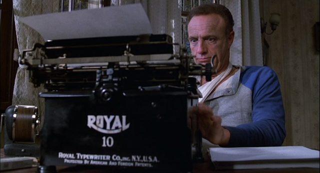Nahaufnahme von Shelton an einer Schreibmaschine in dem Haus von Annie Wilkes.